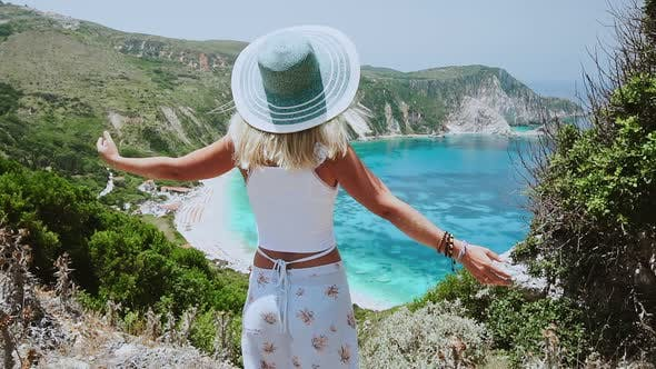 Thumbnail for Woman with Sun Hat Spreading Arms in Front of Beautiful Seascape on Kefalonia Island. Blonde Female