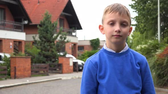 Thumbnail for A Young Boy Looks Seriously at the Camera in a Suburban Street