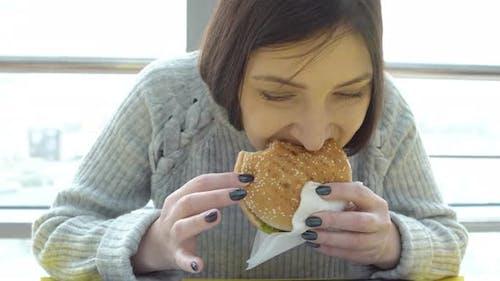 Young Woman Eats a Burger. Harmful Fatty Foods