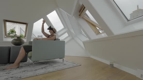 View of Young Blond Woman Sitting on the Side of Arm Chairs Using Tablet Inside of Room in a Cube