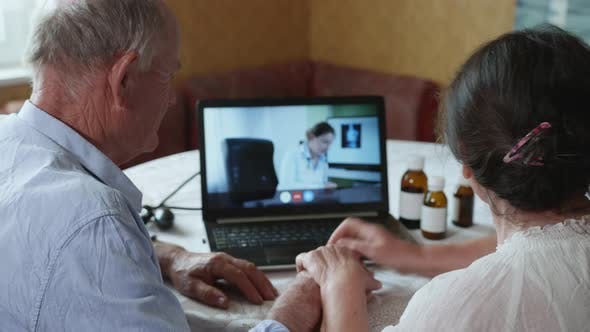 Thumbnail for Doctor Online, an Elderly Married Couple of a Male and Female Consult with a Medical Worker on a