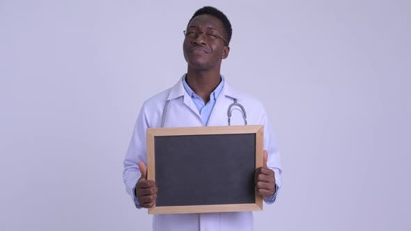 Thumbnail for Young Happy African Man Doctor Thinking While Holding Blackboard