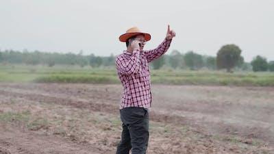 Asian farmer taking a call on smartphone. farmer complaining on a phone call among farm