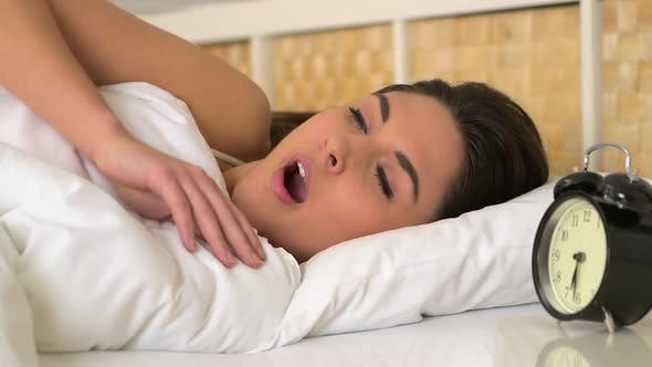 Thumbnail for Woman yawning and waking up in bed