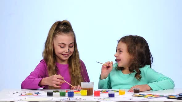 Thumbnail for Two Little Sisters Paint a Picture and Start Drawing on the Face. Close Up. White Background