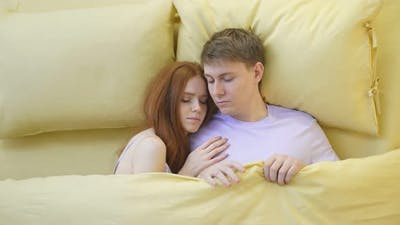 Top View of Beautiful Young Couple Sleeping Together in Bed at Home Yellow Bed