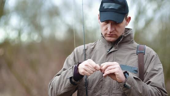 Thumbnail for Confident Man Preparing Fishing Rod at Lakeshore