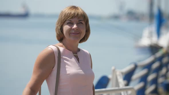 Thumbnail for Cheery Blonde Woman Standing and Smiling at Dnipro River in Summer in Slo-mo
