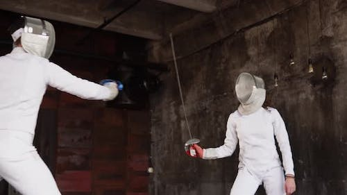 the Man and His Student Are Practicing Fencing, They Keep Swords in Their Hands