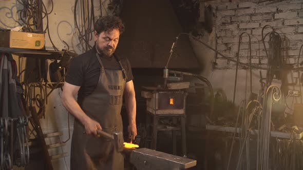 Thumbnail for Portrait of Blacksmith in Working Atmosphere. Man Works with Molten Metal in the Forge