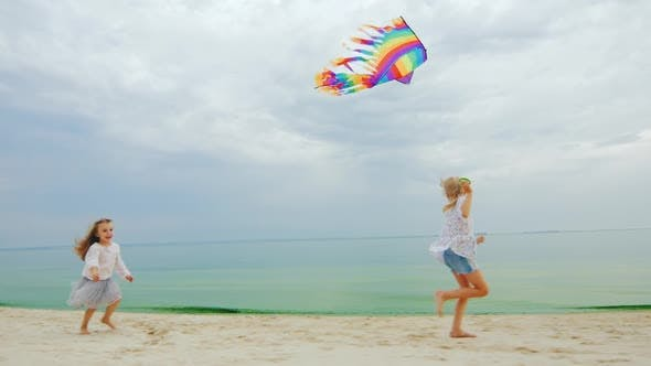 Thumbnail for Two Little Girls Playing on the Beach. Flying a Kite
