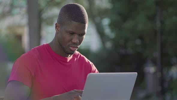 Thumbnail for Young Afro-American Muscular Man Working on Laptop in Park