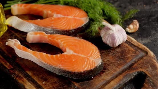 Raw Pieces of Salmon on a Cutting Board with Garlic Rotate.