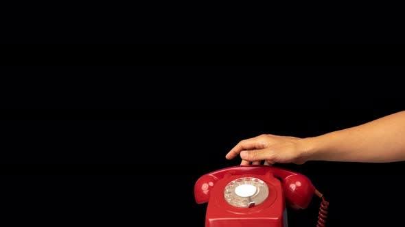 Hand hält den Empfänger eines roten Retro-Telefons