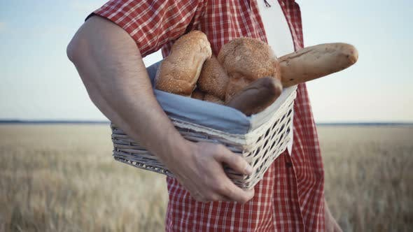 Thumbnail for Young Farmer Are Walking Along the Wheat Field with Bread Baskets