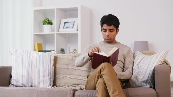 Thumbnail for Man Sitting on Sofa and Reading Book at Home