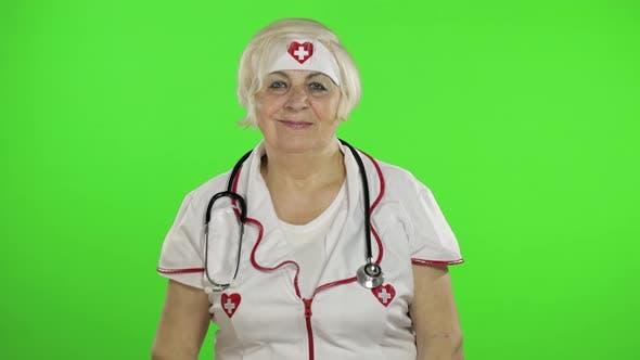 Thumbnail for Ältere kaukasische Ärztin. Krankenschwester. OK Zeichen anzeigen. Daumen nach oben