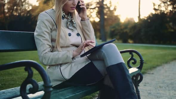 Beautiful Girl on a Bench with Tablet Computer and Cellphone Sitting on Park Bench.