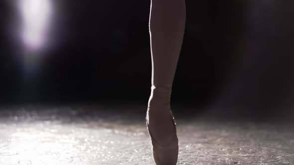 Cover Image for Graceful Ballerina Dancing on Her Pointe Ballet Shoes in Spotlight on Black Background in Studio