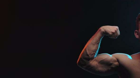 Muskulärer Athlet Flex Bizeps am Arm, zeigt Muskeln. Konzept von Sport und Körper. Im Studio gedreht