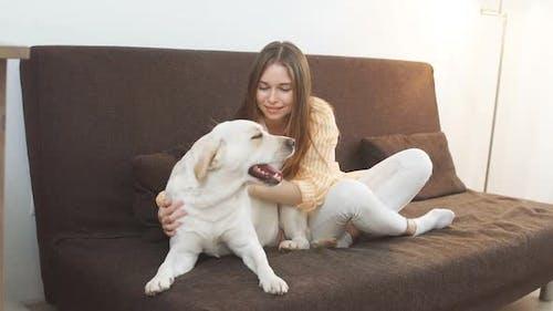 Happy Attractive Girl umarmt einen großen weißen Hund