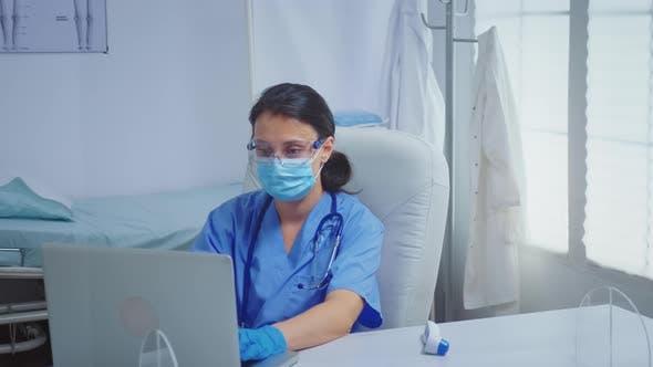 Thumbnail for Nurse Typing on Laptop Wearing Medical Gloves