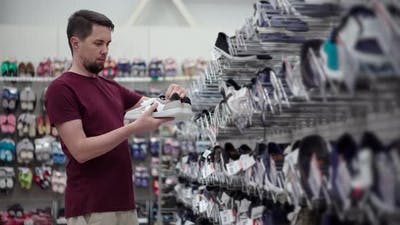 Man is Choosing Sneakers in Hall of Shop of Footwear