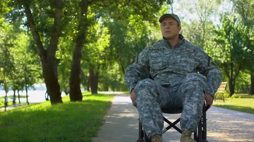 Disabled Young Man in Military Uniform Moving in Wheelchair in City Park, Injury