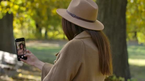 Cover Image for Back View of Young Caucasian Girl in Brown Hat and Coat Taking Selfie on Smart Phone