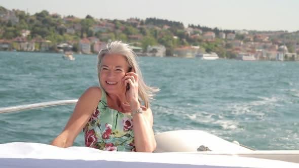 Senior female calling on yacht