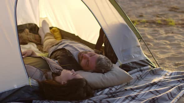 Thumbnail for Loving Couple Lying and Speaking in Tent on Lakeshore at Sunset