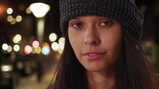 Thumbnail for Millennial girl wearing beanie looking at camera on urban city street at night