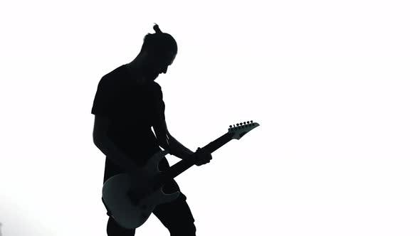 Silhouette of Guitarist Playing Electric Guitar