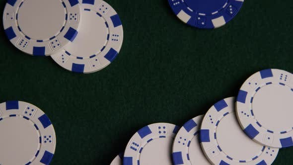 Rotating shot of poker cards and poker chips on a green felt surface - POKER 032