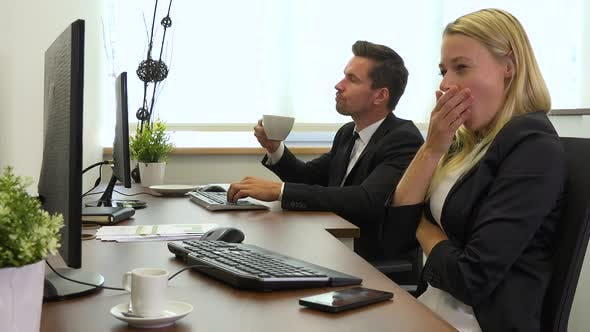 Thumbnail for Two office workers, man and woman, work on computers and get tired
