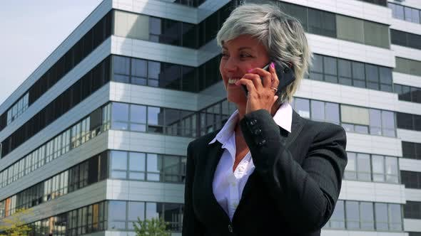 Thumbnail for Business Middle Age Woman Calls with the Smartphone - Company Building in the Background