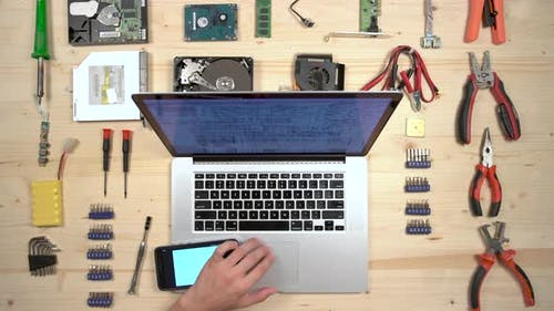 Working on a MacBook at a desk with tools