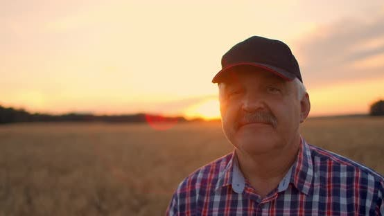 Thumbnail for Close-up Portrait of a Farmer in a Cap at Sunset Looking Directly Into the Camera