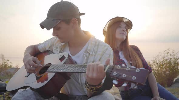 Thumbnail for Hipster Young Guy Playing Guitar and His Girlfriend Listening with Interest on the Background