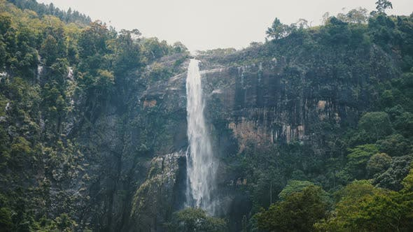Thumbnail for Beautiful Medium Shot, Landscape Background of Large Jungle Waterfall Rushing Down in Exotic