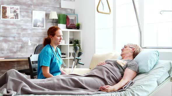 Nurse in Retirement Home Talking with an Old Lady Lying in Hospital Bed