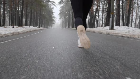 Thumbnail for Legs of Young Attractive Caucasian Girl Running in The Snowy Park in Winter with Headphones