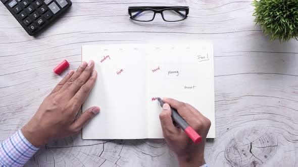 Thumbnail for High Angle View of Man Hand Writing on Weekly Planner on Table.