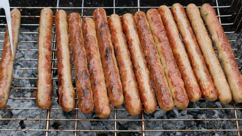 Grilled sausages roasting on barbecue grill, outdoors