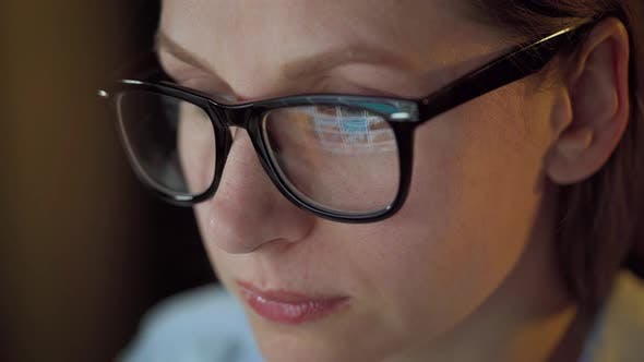 Thumbnail for Woman in Glasses Looking on the Monitor and Surfing Internet. The Monitor Screen Is Reflected