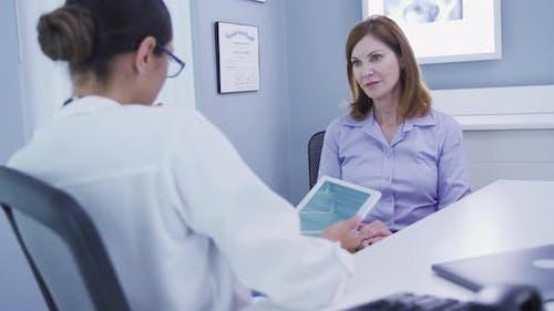 Junge Ärztin diskutieren Krankenversicherung mit älteren Patienten