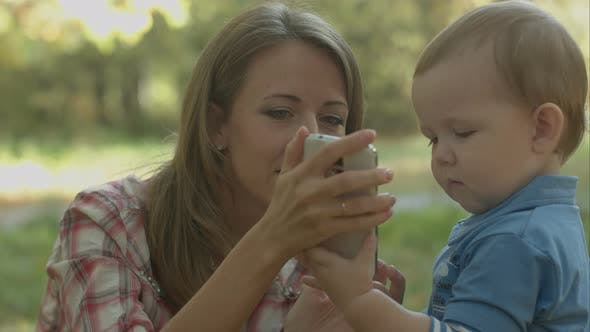 Thumbnail for Mother Helps Little Son To Call His Father with Telephone