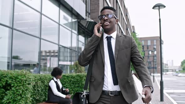 Cover Image for African Businessman Walking and Talking on Phone
