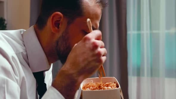 Thumbnail for Close Up of Businessman with Tie Eating Noodles From a Box