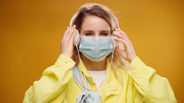 Young Woman Listening to Music with Headphones in Medical Mask Against Yellow Background